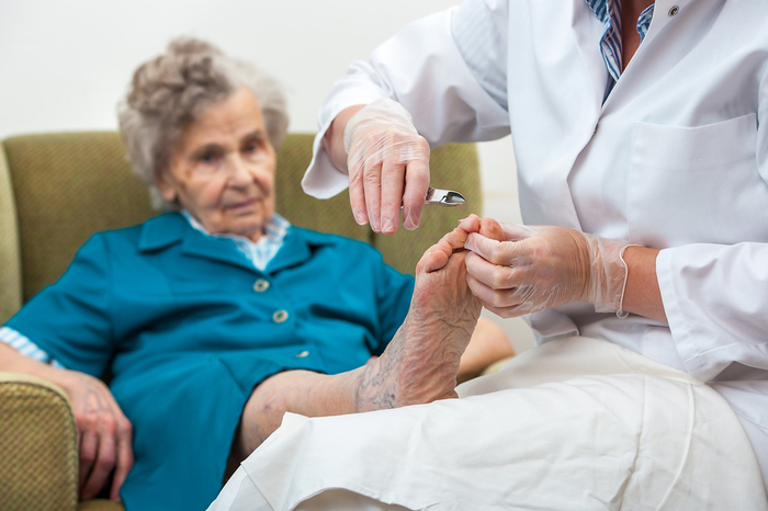 Elderly woman sitting in chair having her toenails clipped.
