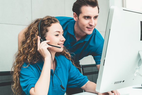 Woman wearing a headset sitting at a desk getting assistance from a colleague.