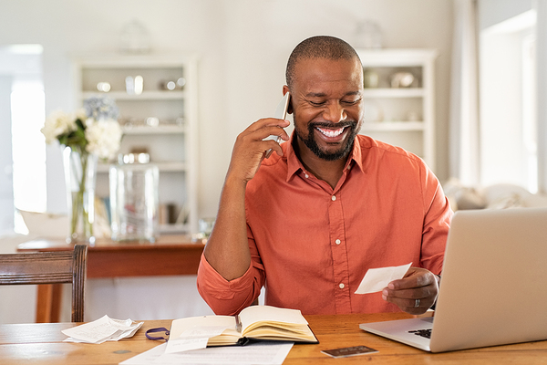 Smiling man talking on the phone while looking at a piece of paper.