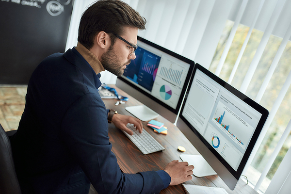 Man sitting at his desk with two desktop computers.