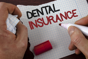 Person writing dental insurance on a piece of paper.