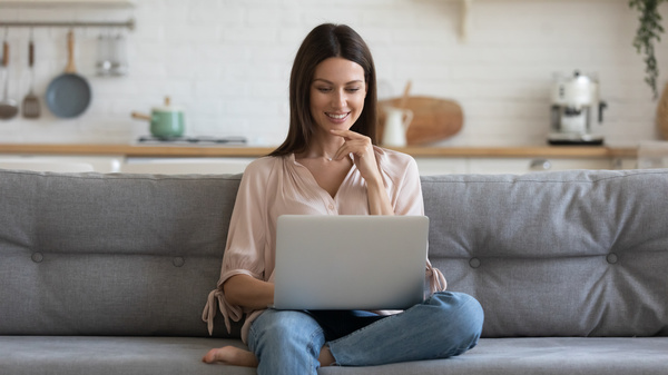 customer experience - sitting on a couch with a laptop.