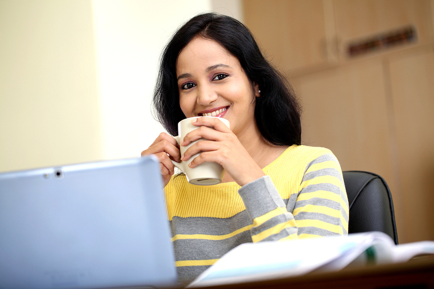 Woman sitting in front of her laptop drinking coffee.