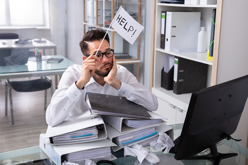 Man sitting at a desk with a pile of binders and a help flag.