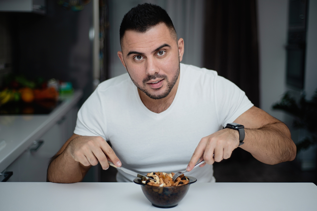 Man sitting at a table eating nuts from a bowl.