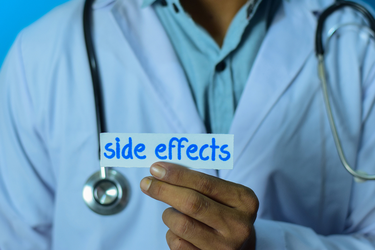 Medical doctor holding a piece of paper labeled side effects.