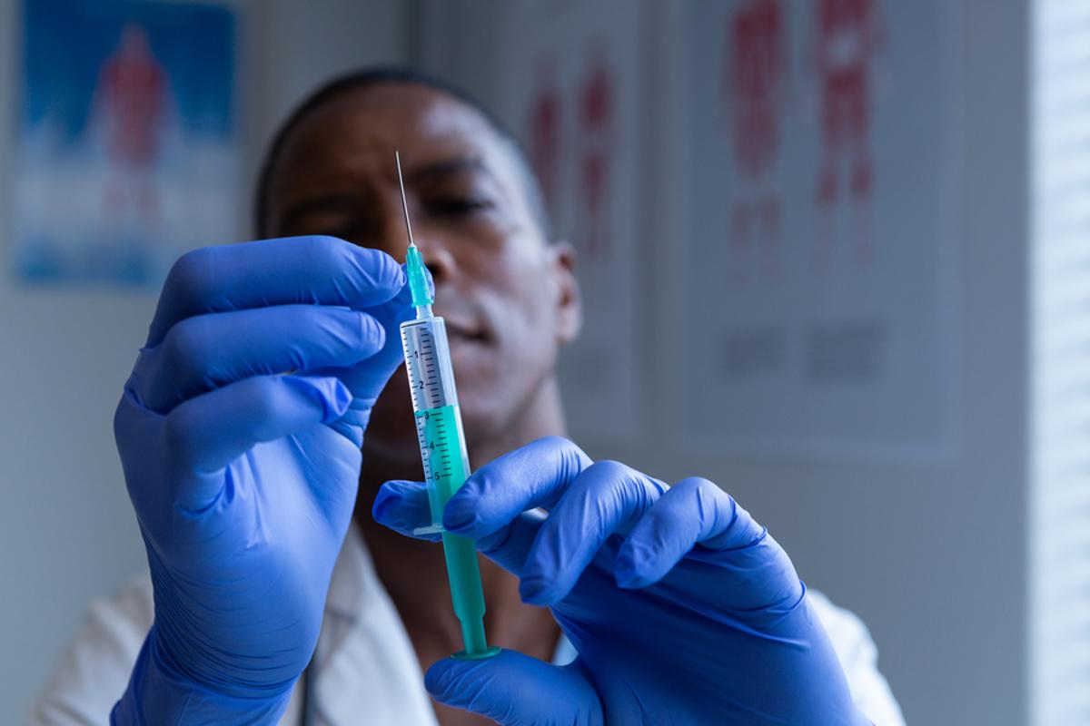 Medical doctor measuring out a medicine dose in a syringe.