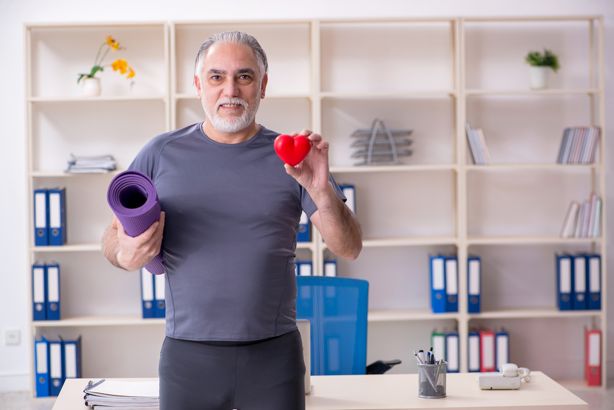 Man holding a yoga mat and a heart shaped object.