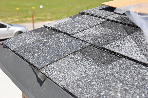 Installing new shingles on a roof.
