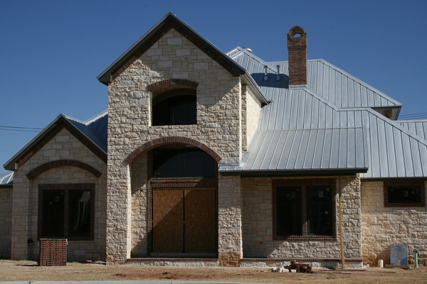 Stone front home with metal roof.