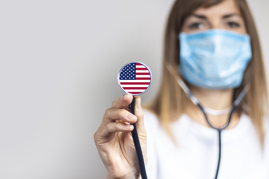 Medical personnel holding a stethoscope with an American flag.