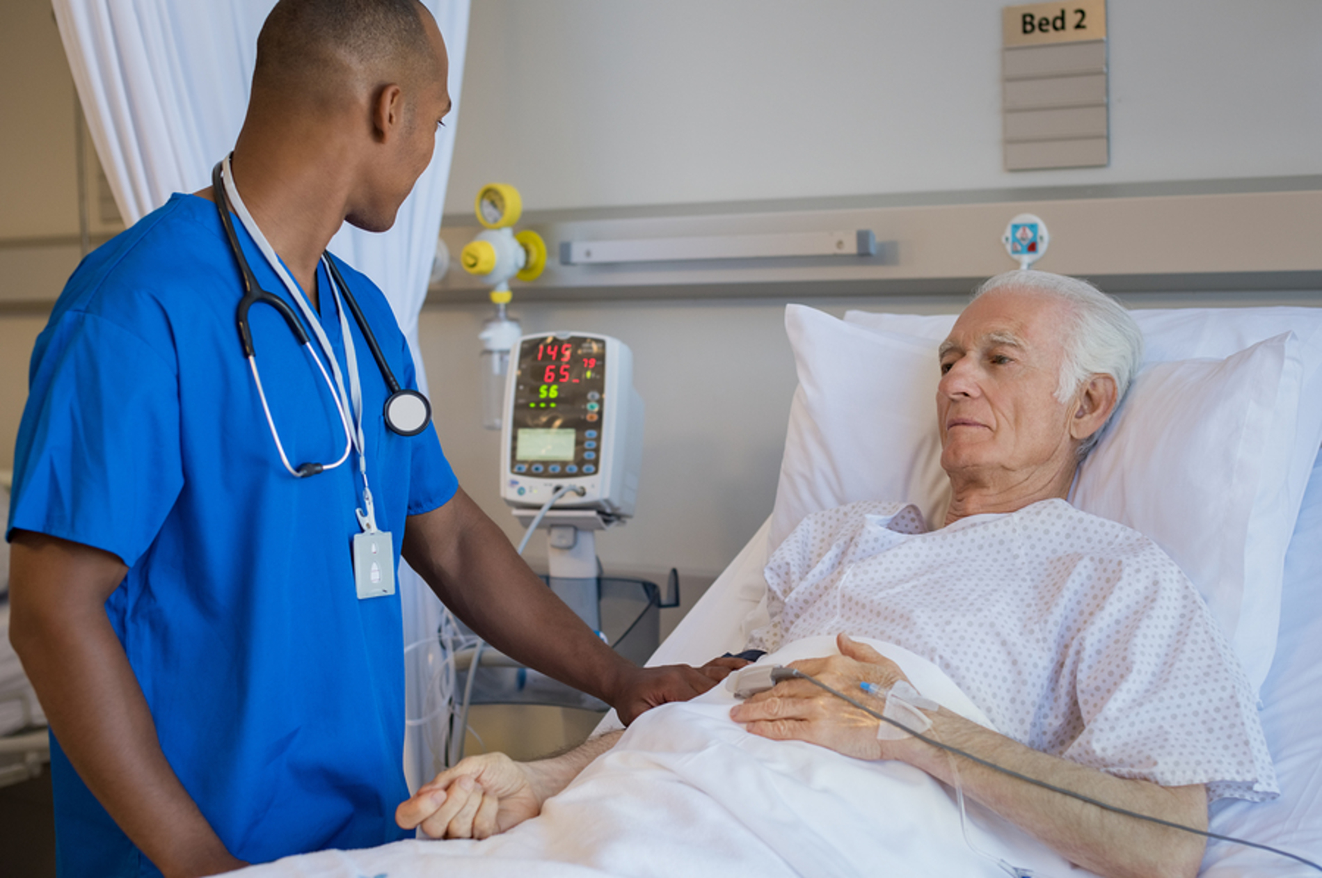 Older male patient getting assistance from a nurse.