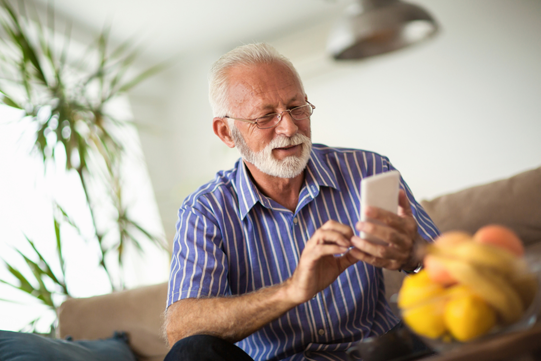 Older man typing on a phone.