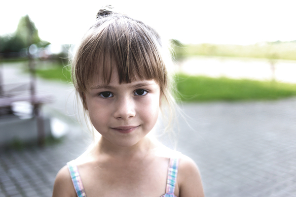 Girl with a slight smile standing outside.