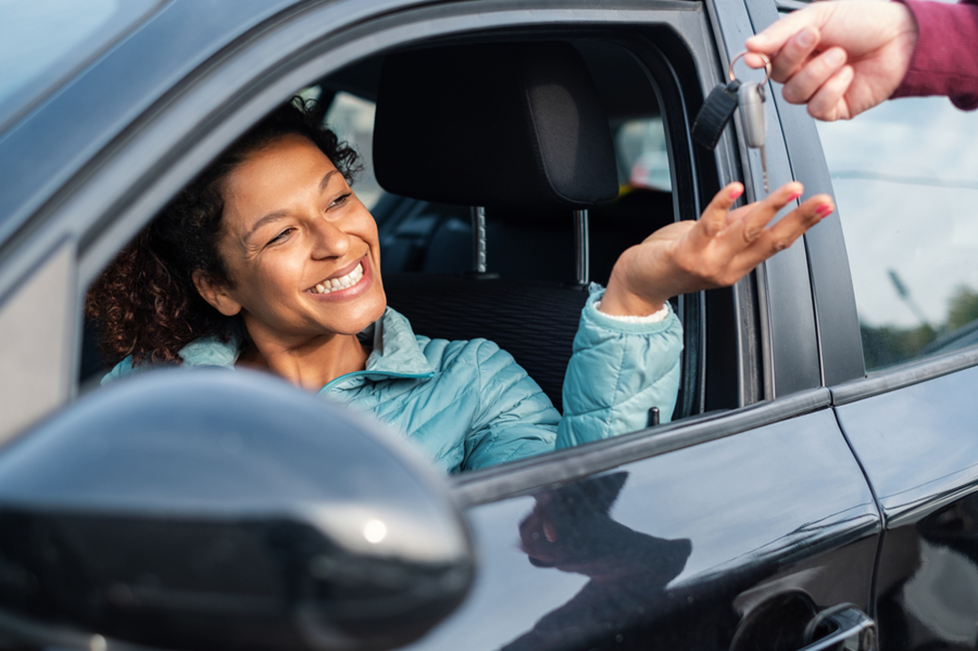 Woman reaching for keys from a car salesman.