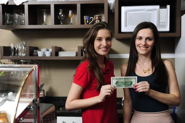 Two women holding their first business earned 10 dollar bill.
