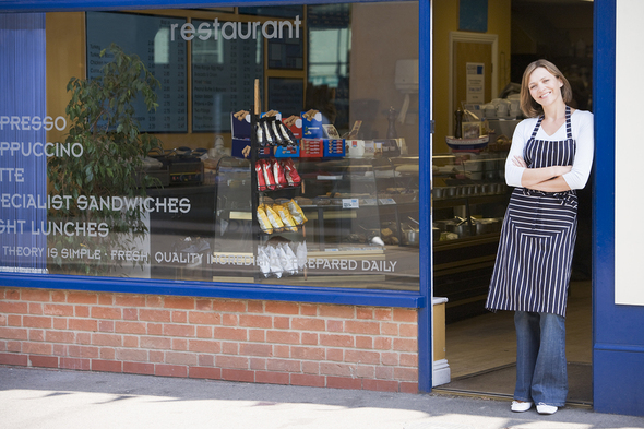 Woman wearing an apron, standing outside a restaurant.