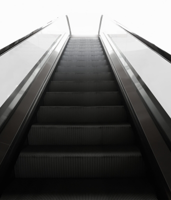 An escalator leading to a bright light
