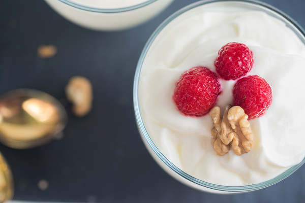 Bowl of yogurt with raspberries and walnuts.