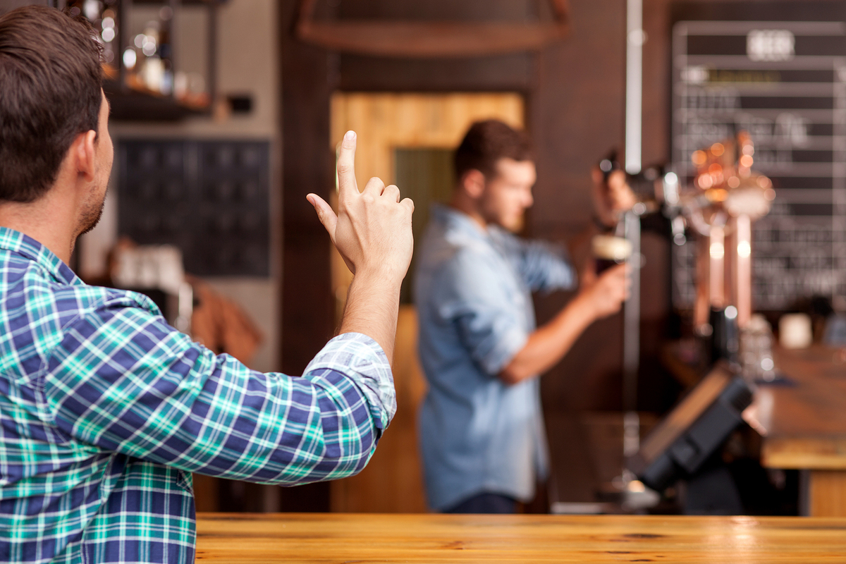 Man flagging a bartender at a pub.