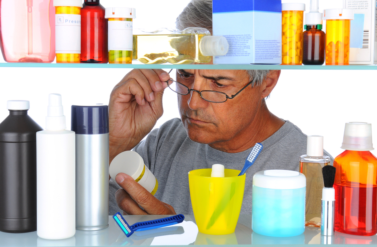 Man looking at a pill bottle label.