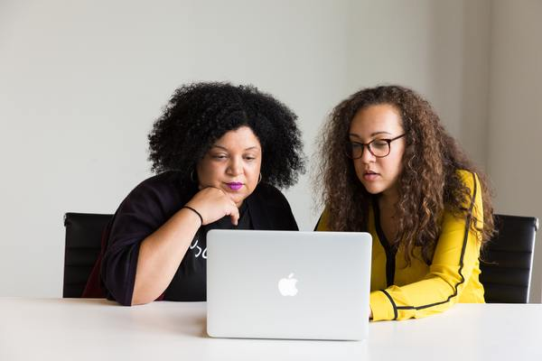 Two women looking at a laptop screen together.