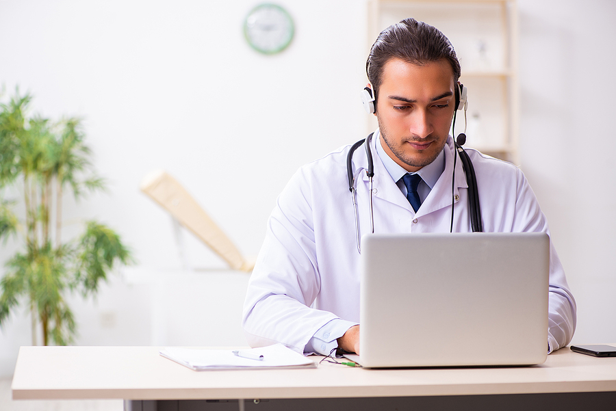 Medical doctor typing on a laptop computer.