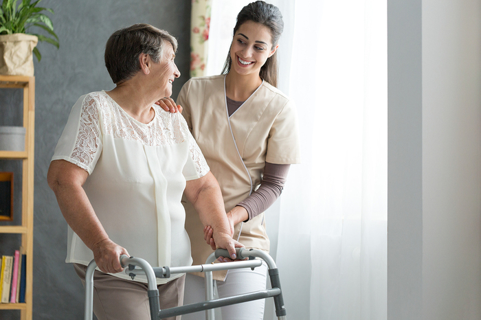 Woman helping an elderly woman with a walker.