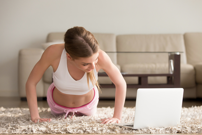 Woman performing pushups while looking at her laptop screen.