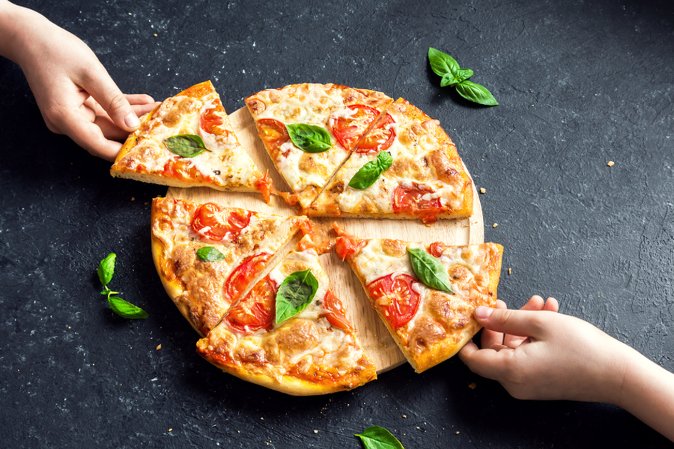 Pizza with whole tomatoes and basil leaves.