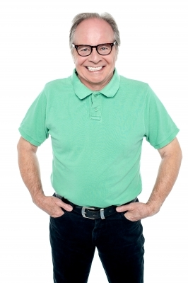 An old person with glasses on, smiling and placing their hands in their pockets