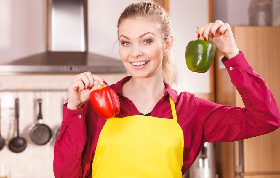 Woman with a yellow apron holding a green and red bell pepper.