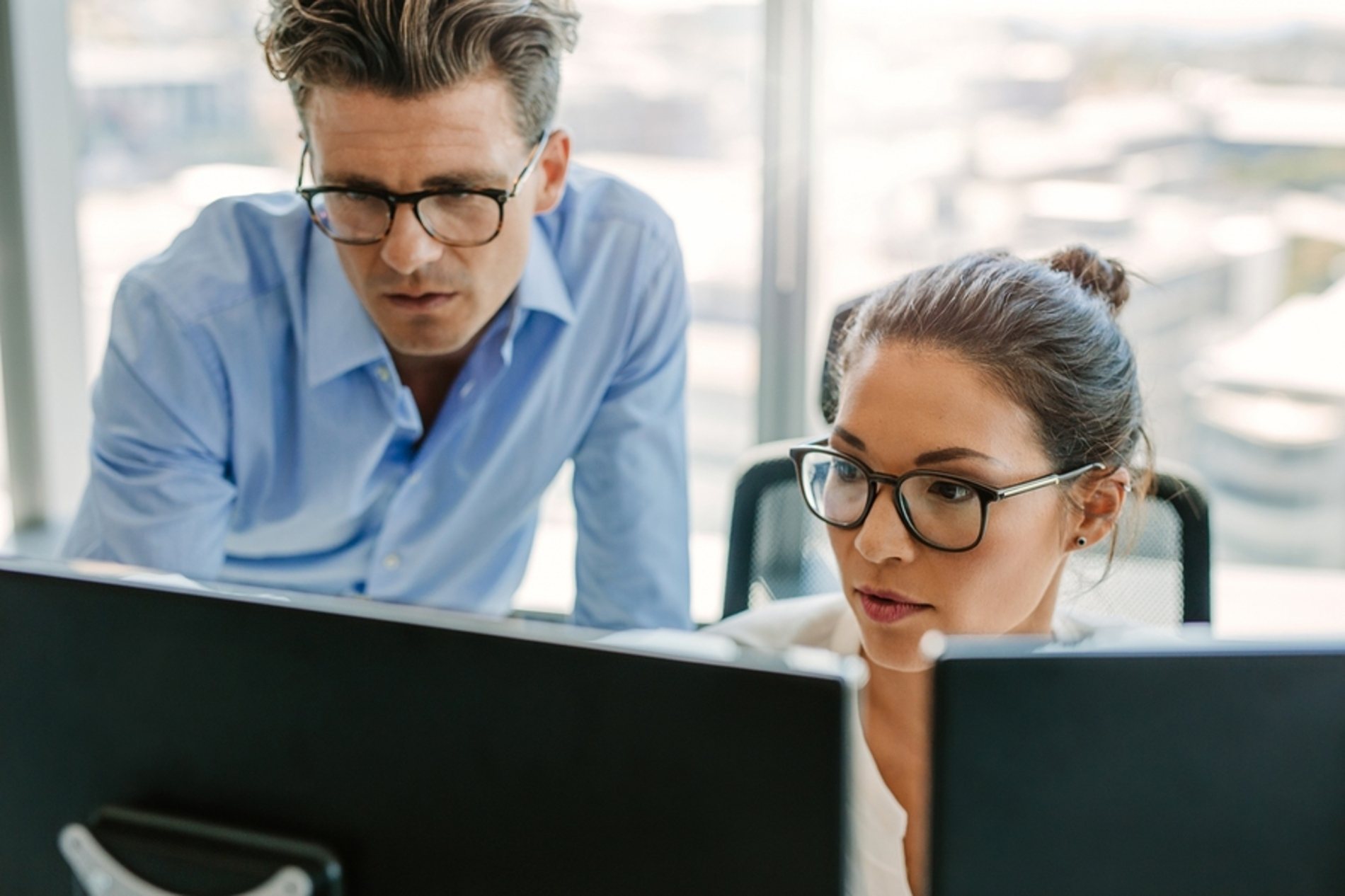 Two coworkers looking at computer monitors together.