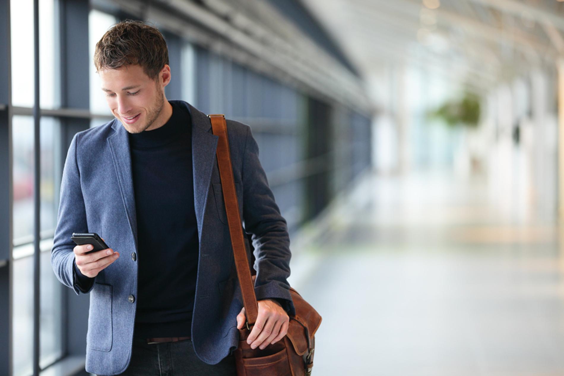 Man walking a hallway looking at his phone.