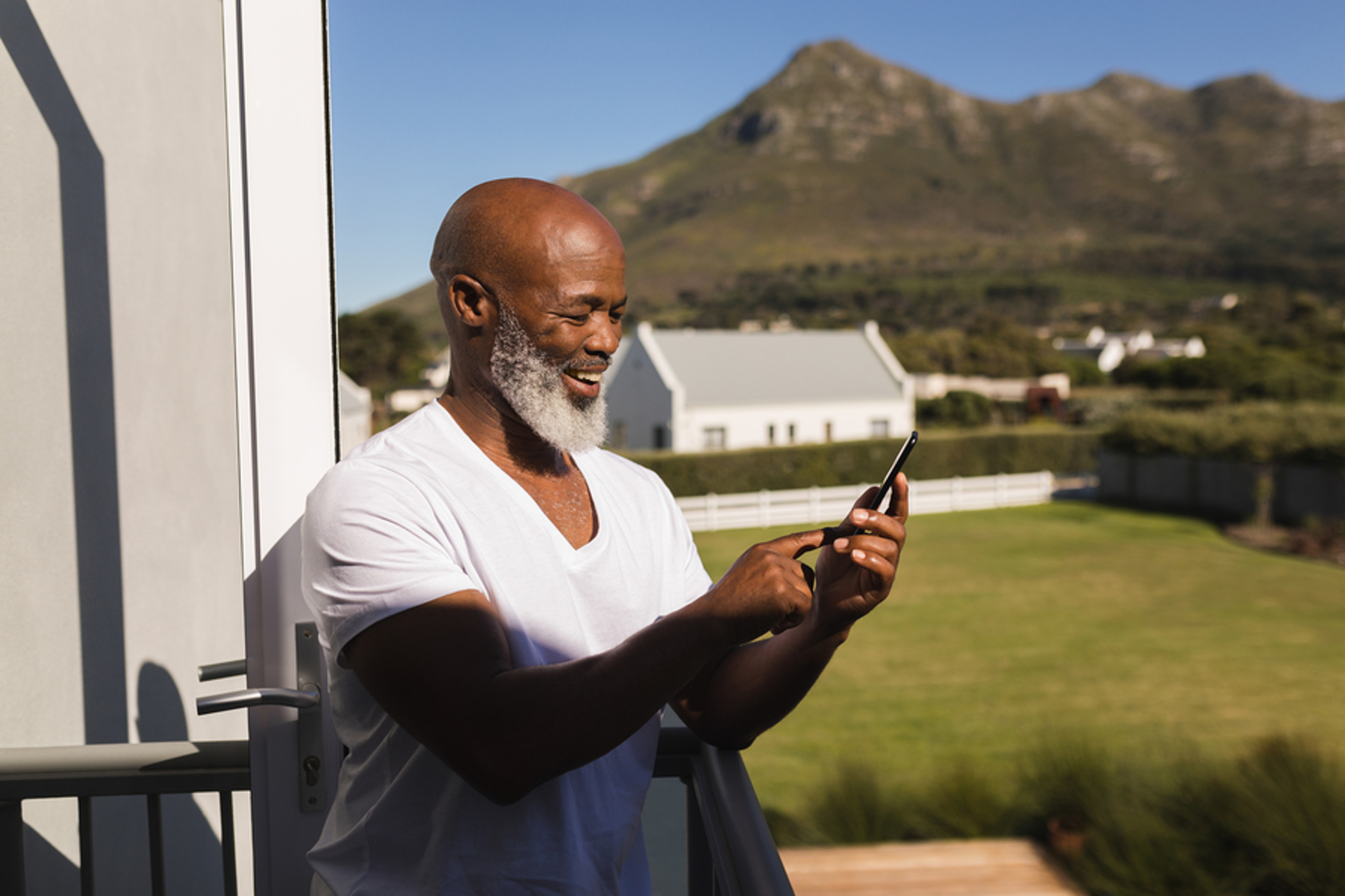 Man looking at a mobile phone while on a deck.