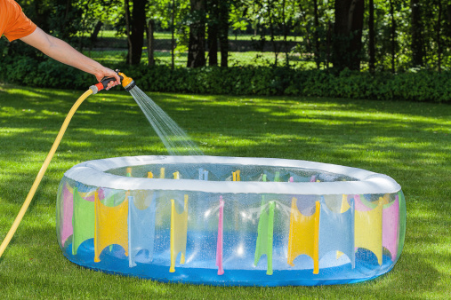Inflated pool with a person spraying water from a hose into it