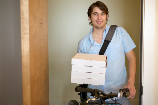 A person delivering rather small boxes of pizza with an unsure smile