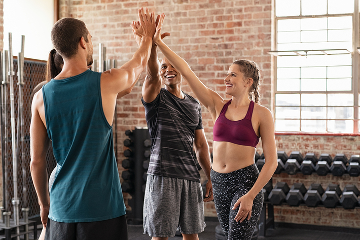 Three people performing a high-five in a gym.