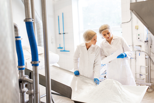 Two woman working in a factory with white coats and blue protective gloves.
