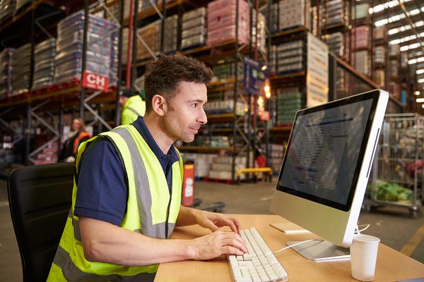 Warehouse employee typing on a desktop computer.