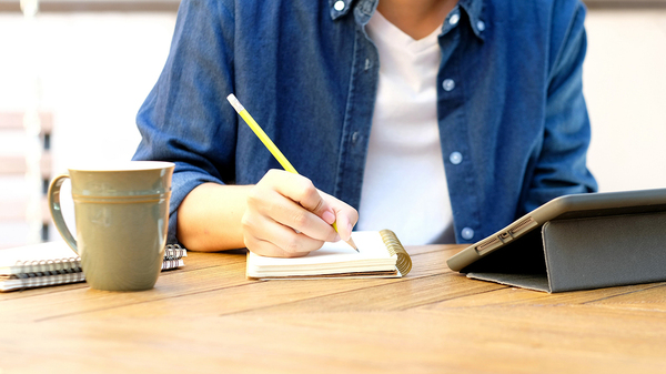 Person sitting at a table writing notes in a note book.