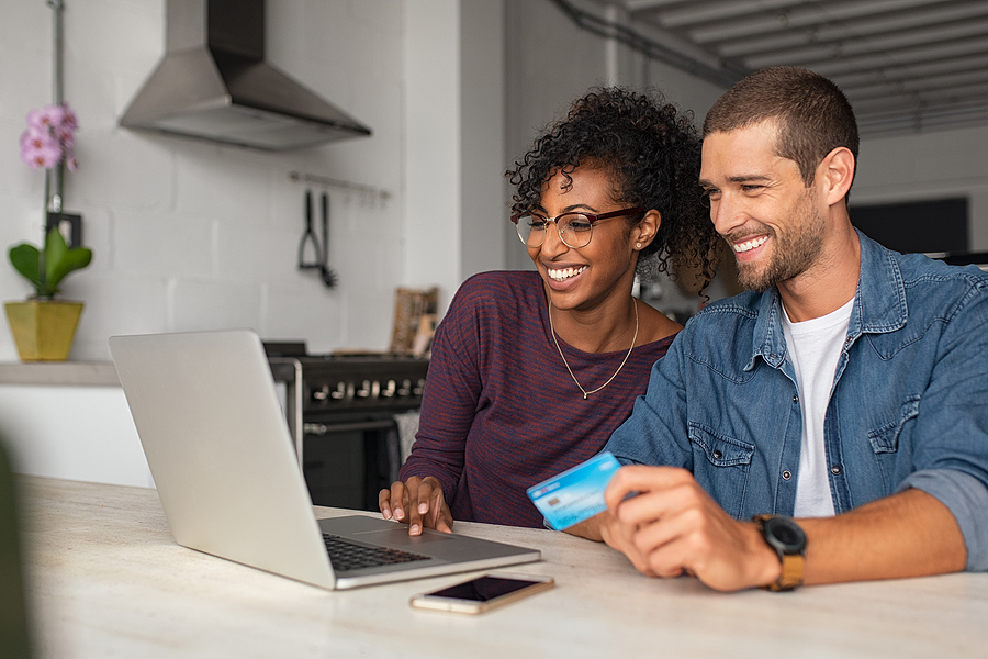 Smiling couple making an online purchase using a credit card.