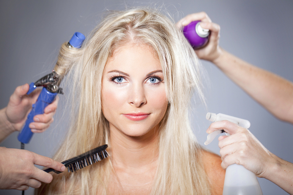 Woman having several people style her hair with irons, brushes and spray bottle.
