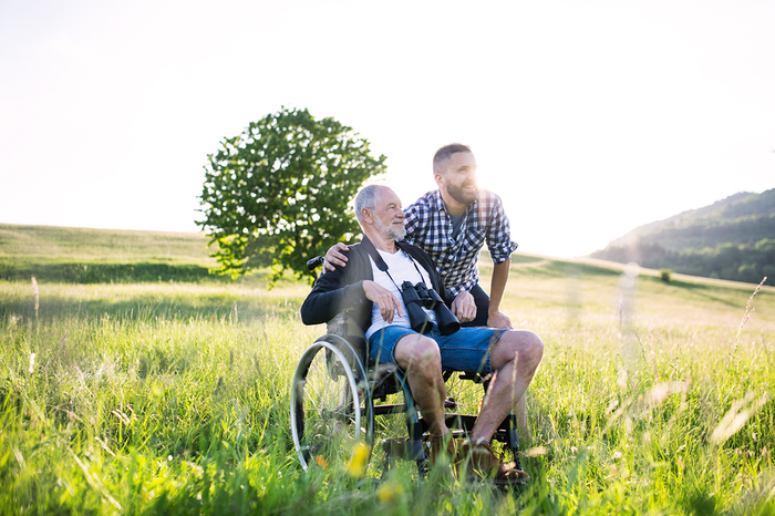 Older man in a wheelchair in a green field.