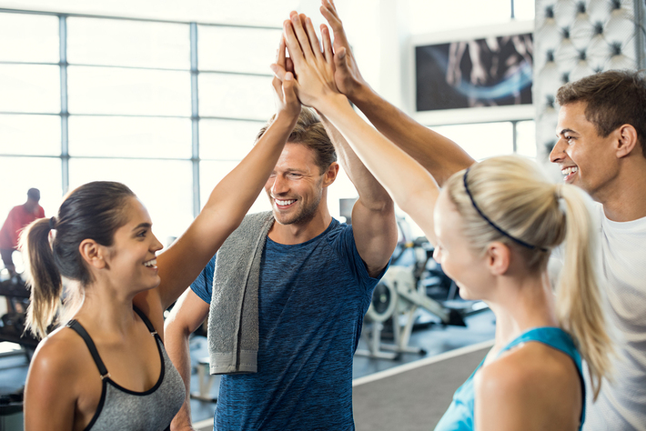 Group of people giving high fives at a gym.