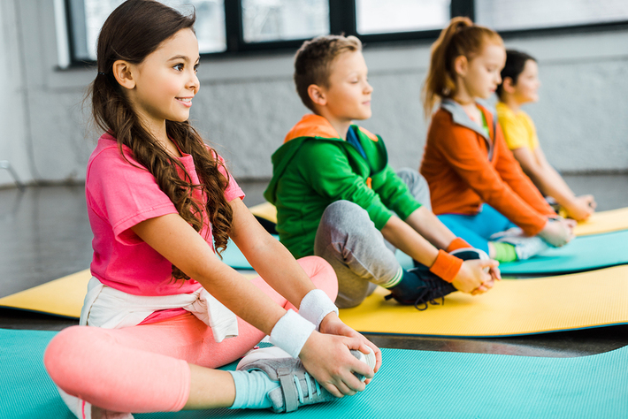 Group of children participating in a yoga class.