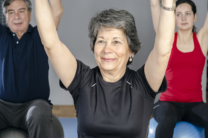 Older woman participating in a fitness class.