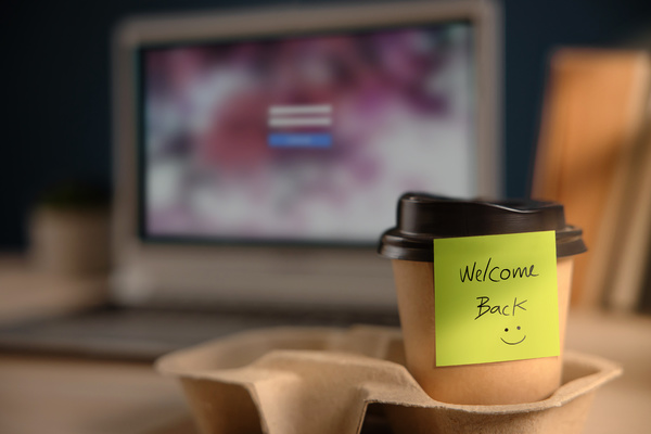 Coffee cup with note welcome back.