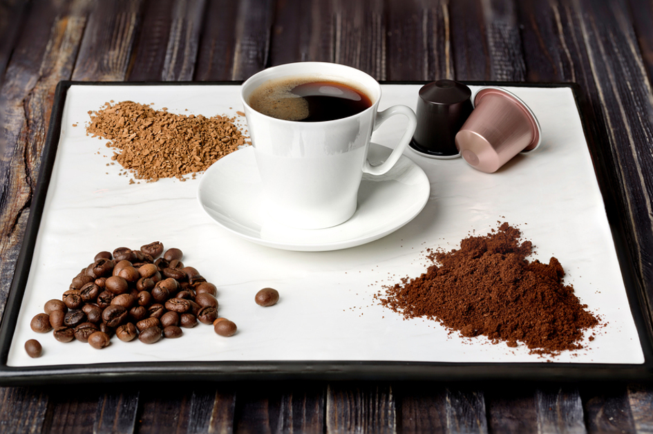 Cup of coffee with coffee beans and cocoa.