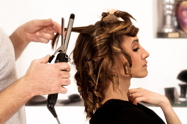 Woman getting her hair curled at a beauty salon.